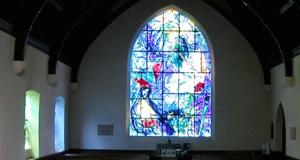 Witraże wielkich malarzy w skromnym kościele.